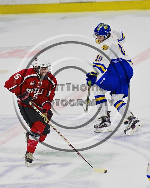 Baldwinsville Bees Isaiah Pompo (5) skates past West Genesee Wildcats Patrick McDonald (18) with the puck in the Section III, Division I Championship game in Boys Ice Hockey at the Utica Auditorium on Sunday, February 28, 2016. West Genesee won 1-0.