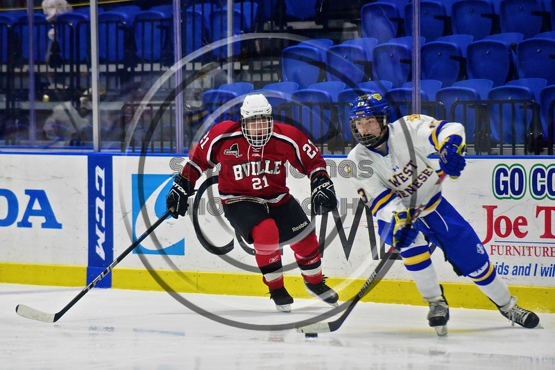Baldwinsville Bees Noah Lindsay (21) closes in on West Genesee Wildcats Ryan Smith (13) in the Section III, Division I Championship game in Boys Ice Hockey at the Utica Auditorium on Sunday, February 28, 2016. West Genesee won 1-0.