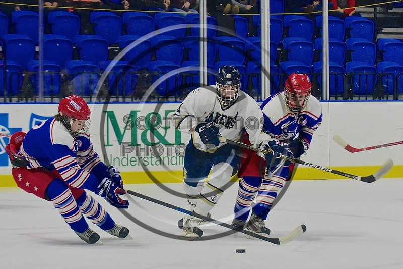 Skaneateles Lakers Reggie Buell (11) being defended by New Hartford Spartans players in the Section III, Division II Championship game at the Utica Auditorium on Sunday, February 28, 2016. Skaneateles won 4-0.