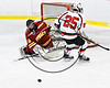 Baldwinsville Bees Jamey Natoli (25) has the puck poked off his stick by Ithaca Little Red goalie William Gephart (30) in NYSPHSAA Section III Boys Ice hockey action at the Lysander Ice Arena in Baldwinsville, New York on Friday, February 9, 2018. Ithaca won 1-0.