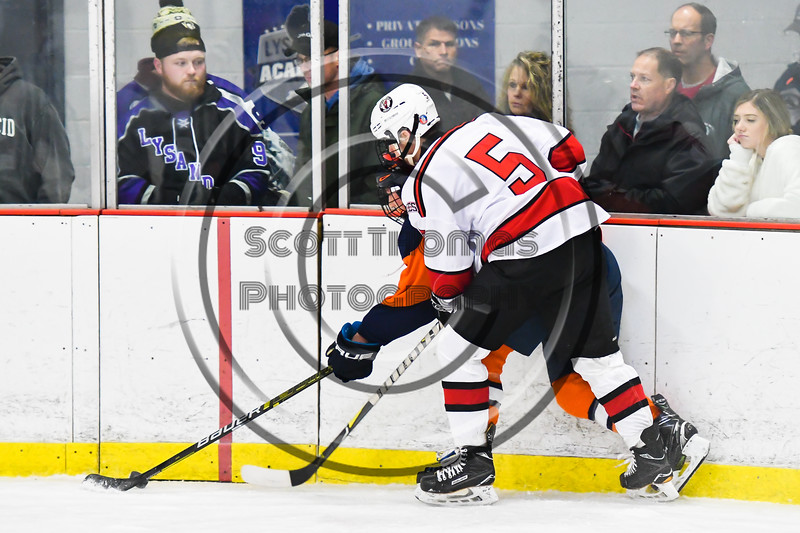 Baldwinsville Bees Alexander Pompo (5) checking a Liverpool Warriors player for the puck in NYSPHSAA Section III Boys Ice Hockey action at the Lysander Ice Arena in Baldwinsville, New York on Thursday, December 6, 2018. Baldwinsville won 5-2.