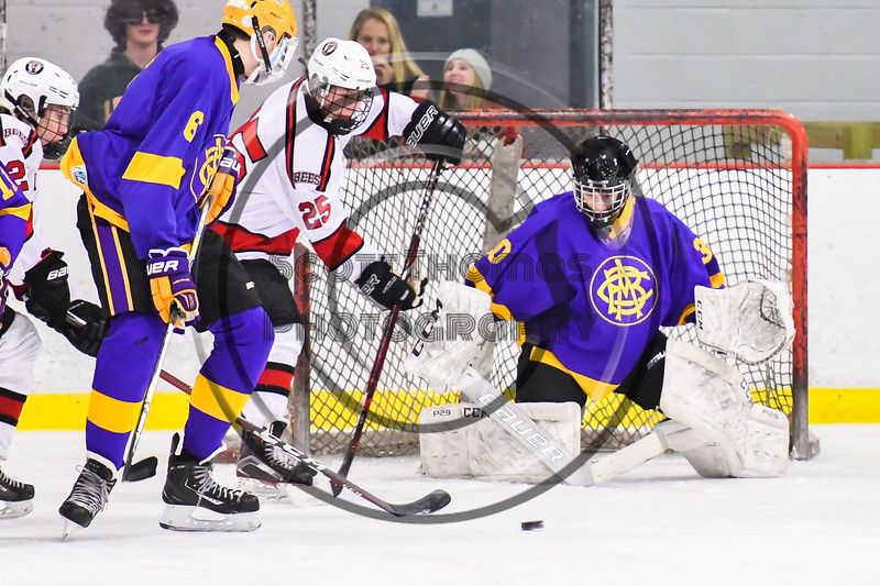Baldwinsville Bees Jamey Natoli (25) goes afater the puck in front of CBA/JD Brothers goalie Joe Salvador (30) in NYSPHSAA Section III Boys Ice Hockey action at the Lysander Ice Arena in Baldwinsville, New York on Tuesday, December 18, 2018. Baldwinsville won 3-1.
