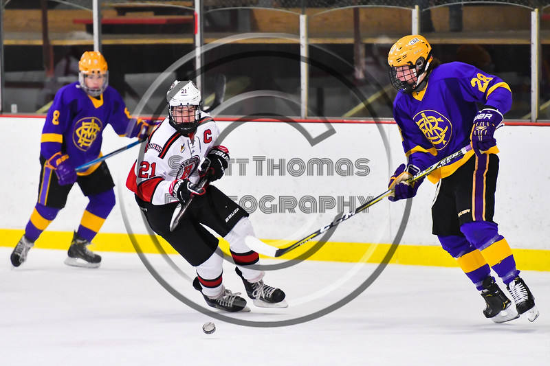 Baldwinsville Bees Cameron Sweeney (21) avoids a check by CBA/JD Brothers Bailey Doust (28) in NYSPHSAA Section III Boys Ice Hockey action at the Lysander Ice Arena in Baldwinsville, New York on Tuesday, December 18, 2018. Baldwinsville won 3-1.