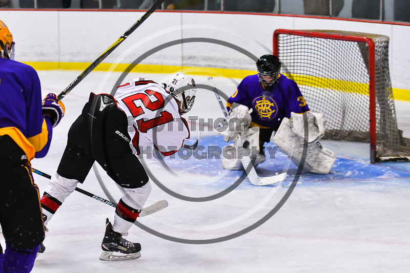 Baldwinsville Bees Cameron Sweeney (21) shot is blocked by CBA/JD Brothers goalie Joe Salvador (30) in NYSPHSAA Section III Boys Ice Hockey action at the Lysander Ice Arena in Baldwinsville, New York on Tuesday, December 18, 2018. Baldwinsville won 3-1.