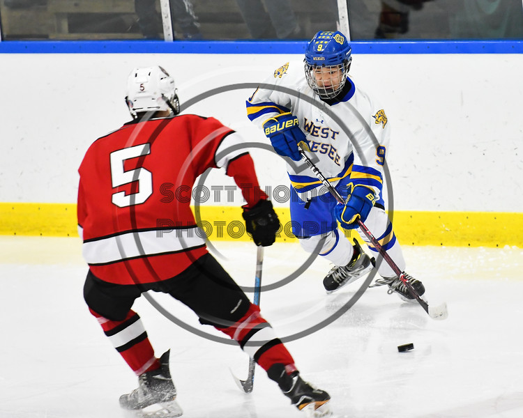 West Genesee Wildcats Joe McLaughlin (9) passes the puck against Baldwinsville Bees Alexander Pompo (5) in NYSPHSAA Section III Boys Ice hockey action at Shove Park in Camillus, New York on Tuesday, January 29, 2019. West Genesee won 5-1.