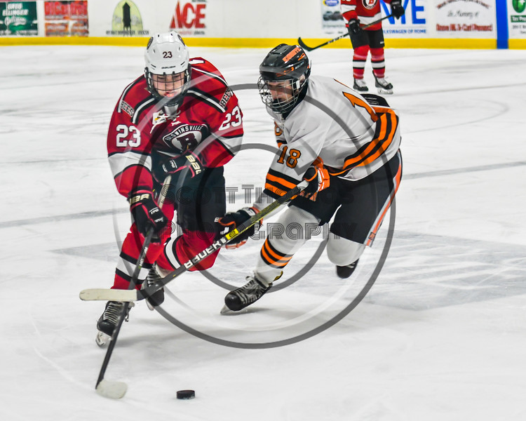 Baldwinsville Bees Braden Lynch (23) being defended by Rome Free Academy Black Knights Aaron Russell (18) in NYSPHSAA Section III Boys Ice hockey playoff action at John F. Kennedy Civic Arena in Rome, New York on Friday, February 15, 2019. Baldwinsville won 5-3.