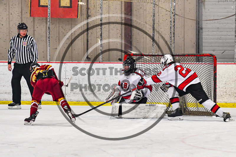 Baldwinsville Bees goalie Jon Schirmer (1) makes a save against Ithaca Little Red Eli Simons (23) in NYSPHSAA Section III Boys Ice Hockey action at the Lysander Ice Arena in Baldwinsville, New York on Tuesday, January 14, 2020. Ithaca won 3-2.