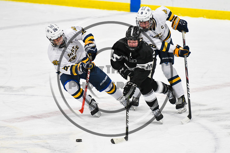 Syracuse Cougars Ryan Durand (10) with the puck against West Genesee Wildcats defenders Billy Fisher (8) and Max Hahn (28) in a NYSPHSAA Section III Boys Ice hockey game at Shove Park in Camillus, New York on Wednesday, January 22, 2020. Game ended in a 1-1 tie.