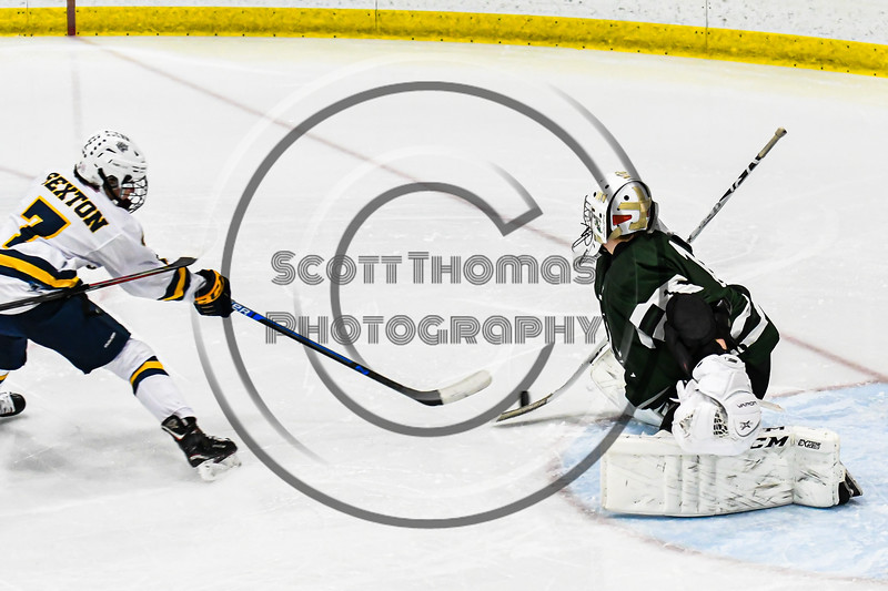Fayetteville-Manlius Hornets goalie Konrad Walberger (1) makes a stick save against West Genesee Wildcats Liam Sexton (7) in a NYSPHSAA Section III Boys Ice hockey playoff game at the Shove Park in Camillus, New York on Wednesday, February 26, 2020. West Genesee won 4-1.