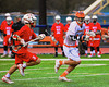 Liverpool Warriors Kendall Keahey (12) being chased by Baldwinsville Bees Stephen Petrelli (9) in Boys Lacrosse on Tuesday, April 29, 2014 at Liverpool, New York, Liverpool won 14-13 in overtime.