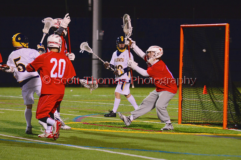 West Genesee Wildcats Mat Milne (5) fires in a goal past Baldwinsville Bees goalie Daniel Thomas (15) in Boys Lacrosse on Tuesday, April 8, 2014 at Camillus, New York. West Genesee won 8-5.