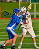 Baldwinsville Bees Connor Chapman (12) checks an Oswego Buccaneers player in Section III Boys Lacrosse action in Fulton, New York on Thursday, May 1, 2014.  Baldwinsville won 13-9.