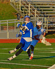 Oswego Buccaneers Ryan Martin (5) gets past Baldwinsville Bees defender Luke McCaffrey (20) in Section III Boys Lacrosse action in Fulton, New York on Thursday, May 1, 2014.  Baldwinsville won 13-9.