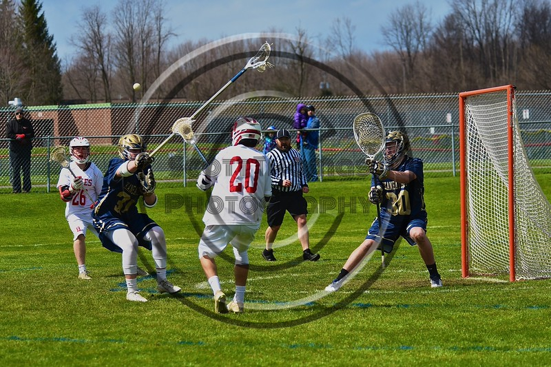 Baldwinsville Bees Ryan Gebhardt (20) passing the ball to Connor Smith (26) over a Skaneateles Lakers defender in Section III Boys Lacrosse action at the Pelcher-Arcaro Stadium in Baldwinsville, New York on Saturday, April 2, 2016.  Baldwinsville won 10-6.