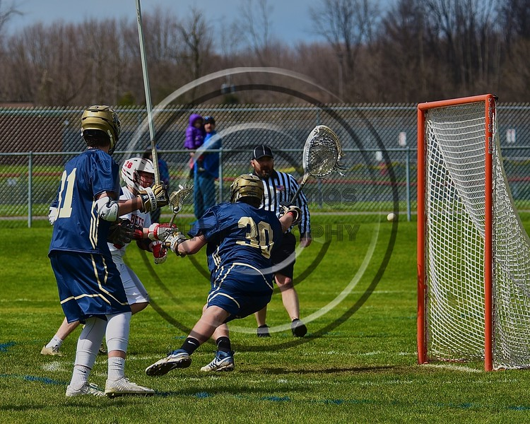 Baldwinsville Bees Connor Smith (26) fires the ball past Skaneateles Lakers goalie Kyle Oschner (30) for a goal in Section III Boys Lacrosse action at the Pelcher-Arcaro Stadium in Baldwinsville, New York on Saturday, April 2, 2016.  Baldwinsville won 10-6.