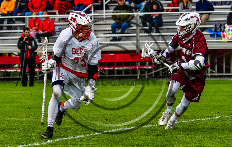 Baldwinsville Bees Brandon Kohutanich (25) protecting the ball from an Auburn Maroons defender in Section III Boys Lacrosse action at the Pelcher-Arcaro Stadium in Baldwinsville, New York on Monday, May 2, 2016.  Baldwinsville won 16-6.