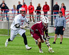 Auburn Maroons Kevin Munn (3) scoops up a ground ball as Baldwinsville Bees Ryan ingerson (3) gives chase in Section III Boys Lacrosse action at the Pelcher-Arcaro Stadium in Baldwinsville, New York on Monday, May 2, 2016.  Baldwinsville won 16-6.