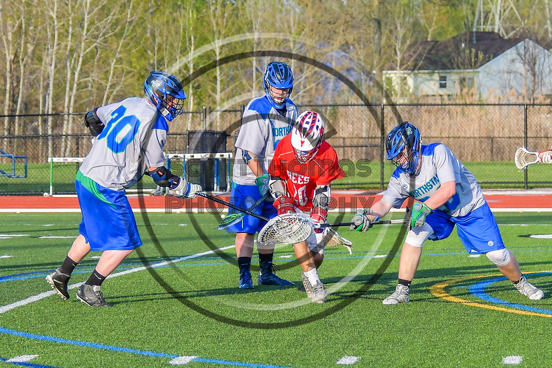 Baldwinsville Bees Ryan Gebhardt (20) battles for the ball with Cicero-North Syracuse Northstars goalie Hunter Dorgan and Noah Gessini (30) in Section III Boys Lacrosse action at the Bragman Stadium in Cicero, New York on Thursday, May 12, 2016.  Baldwinsville won 7-6 in OT.