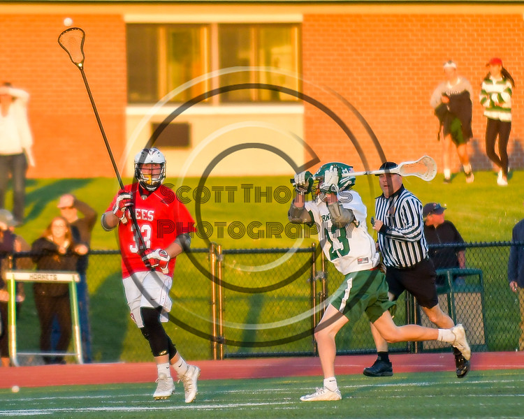 Baldwinsville Bees John Petrelli (33) passes the ball over Fayetteville-Manlius Hornets Dan Burnam (23) in Section III Boys Lacrosse action at the Fayetteville-Manlius High School in Manlius, New York on Wednesday, May 18, 2016.  Fayetteville-Manlius won 9-8.