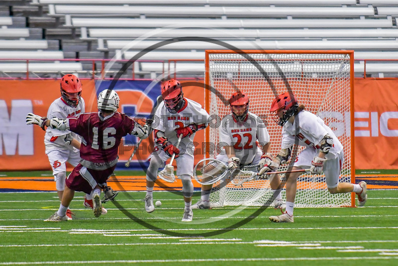 Auburn Maroons Brian Cunningham (16) gets the ball knocked away from him by Jamesville-Dewitt Red Rams defenders in Section III Boys Class B Lacrosse Championship action at the Carrier Dome in Syracuse, New York on Saturday, May 28, 2016.  Jamesville-Dewitt won 15-7.
