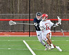 Baldwinsville Bees Austin Bolton (15) protects the ball from a Pittsford Panthers defender in Section III Boys Lacrosse action at the Pelcher-Arcaro Stadium in Baldwinsville, New York on Saturday, April 7, 2018.  Baldwinsville won 14-6.