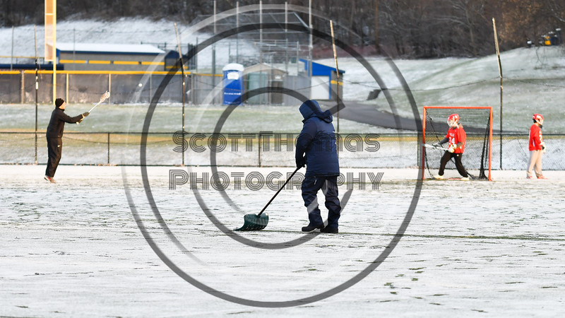 A volunteer clears the center line of snow on Mike Messere Field in Camillus, New York on Tuesday, April 17, 2018 before the Baldwinsville Bees played the West Genesee Wildcats in a Section III Boys Lacrosse game.