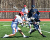 Baldwinsville Bees Cole Peters (11) shoots the ball past a Homer Trojans defender in Section III Boys Lacrosse action at the Pelcher-Arcaro Stadium in Baldwinsville, New York on Saturday, April 21, 2018.  Homer won 13-10.