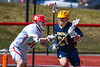 Baldwinsville Bees Caleb Voorhees (17) defending against Victor Blue Devils Camden Hay (21) in Section III Boys Lacrosse action at the Pelcher-Arcaro Stadium in Baldwinsville, New York on Friday, April 6, 2019.  Victor won 9-7.
