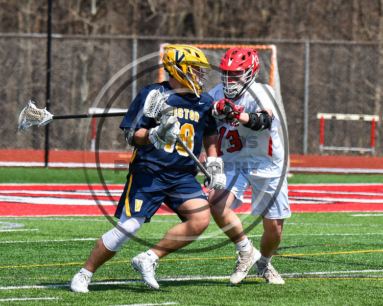 Baldwinsville Bees Braden Lynch (13) defending against Victor Blue Devils Joey Pezzimenti (19) in Section III Boys Lacrosse action at the Pelcher-Arcaro Stadium in Baldwinsville, New York on Friday, April 6, 2019.  Victor won 9-7.