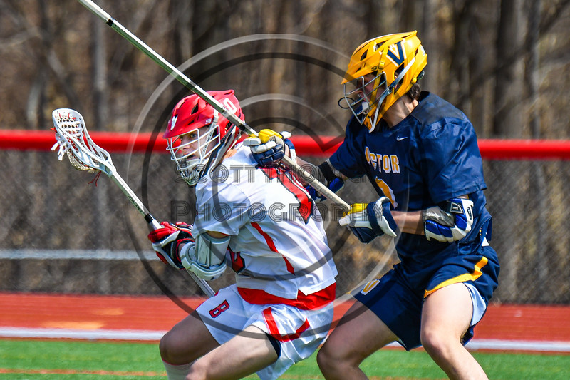 Baldwinsville Bees Spencer Wirtheim (10) with the ball against a Victor Blue Devils defender in Section III Boys Lacrosse action at the Pelcher-Arcaro Stadium in Baldwinsville, New York on Friday, April 6, 2019.  Victor won 9-7.