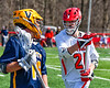 Baldwinsville Bees Cameron Sweeney (21) defending against a Victor Blue Devils player in Section III Boys Lacrosse action at the Pelcher-Arcaro Stadium in Baldwinsville, New York on Friday, April 6, 2019.  Victor won 9-7.