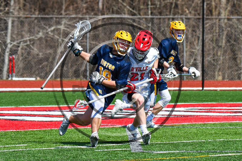 Baldwinsville Bees Cameron Sweeney (21) defending against Victor Blue Devils Joey Pezzimenti (19) in Section III Boys Lacrosse action at the Pelcher-Arcaro Stadium in Baldwinsville, New York on Friday, April 6, 2019.  Victor won 9-7.