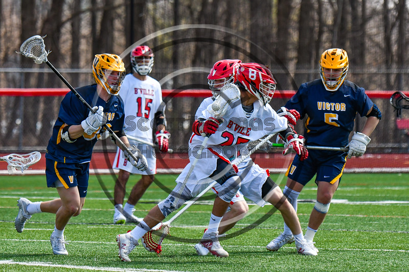 Baldwinsville Bees Cameron Slink (25) with the ball against the Victor Blue Devils in Section III Boys Lacrosse action at the Pelcher-Arcaro Stadium in Baldwinsville, New York on Friday, April 6, 2019.  Victor won 9-7.