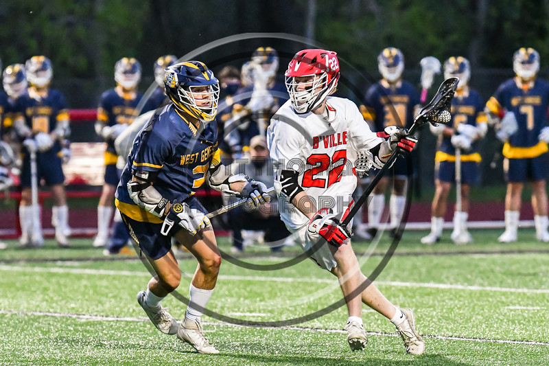 Baldwinsville Bees Carson Dyl (22) being defended by  West Genesee Wildcats Jack Mellen (3) in Section III Boys Lacrosse action at the Pelcher-Arcaro Stadium in Baldwinsville, New York on Tuesday, May 4, 2021. Baldwinsville won 11-4.