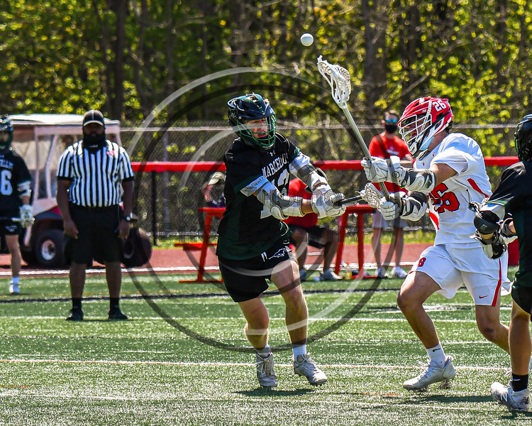 Baldwinsville Bees Colin Socker (26) gets a shot off over Marcellus Mustangs Ryan Moses (13) in Section III Boys Lacrosse action at the Pelcher-Arcaro Stadium in Baldwinsville, New York on Saturday, May 15, 2021. Baldwinsville won 17-4.