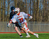 Baldwinsville Bees Luke McCaffrey (20) fends of a check by a Corcoran Cougars defender in Section III Boys Lacrosse action at the Pelcher-Arcaro Stadium in Baldwinsville, New York.  Baldwinsville won 10-1.