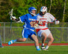 Baldwinsville Bees Ronnie May (26) checks an Oswego Buccaneers player in Section III Boys Lacrosse action at the Pelcher-Arcaro Stadium in Baldwinsville, New York.  Baldwinsville won 9-3.