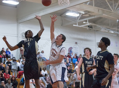 Lyman Hall's Pat Doherty puts up a shot as Platt's Isaiah Jones tries to block Tuesday at Lyman Hall High School in Wallingford The Platt Panthers defeated the Lyman Hall Trojans 93 to 79.December,27 2016 © 2016 Justin Weekes