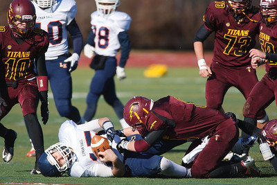 Lyman Hall's quarter back Kyle Smith (15) gets sacked by Sheehan's Danny Deleonardo (8) Thursday at Riccitelli Field in Wallingford November,28 2013 | Justin Weekes / For the Record-Journal