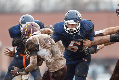 Lyman Hall's Dylan Koval (67) gets a hole of Sheehan's Zach Davis (27) Thursday during the Carini Bowl at Fitzgerald Field in Wallingford Nov 27, 2014 | Justin Weekes / For the Record-Journal