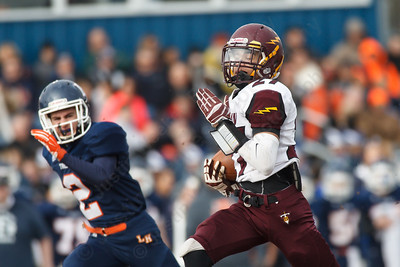 Sheehan's Zach Davis (27) check over his shoulder on a run for a touch down in the first quarter as Lyman Hall's Pat Patrell (2) chases Thursday during the Carini Bowl at Fitzgerald Field in Wallingford Nov 27, 2014 | Justin Weekes / For the Record-Journal