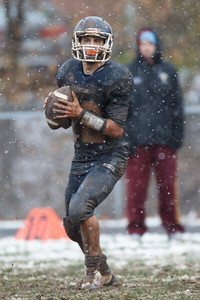 Lyman Hall's Stephen Grammatico (12) drops back to pass late in the fourth quarter as the snow began to fall Thursday during the Carini Bowl at Fitzgerald Field in Wallingford Nov 27, 2014 | Justin Weekes / For the Record-Journal