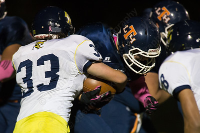 Lyman Hall's Nick Santello (24) gets stopped by East Haven's Noah Fiorillo (33) Thursday at Riccitelli Field in Wallingford Oct. 15, 2015 | Justin Weekes / For the Record-Journal