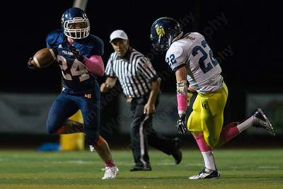 Lyman Hall's Nick Santello (24) rolls right as East Haven's McClay Marshall (22) chases Thursday at Riccitelli Field in Wallingford Oct. 15, 2015 | Justin Weekes / For the Record-Journal
