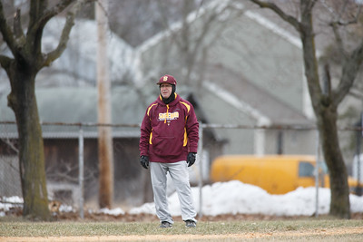 Sheehan's Matt Altieri keeps warm by wearing gloves and extra layers on the third baseline in 30 degree weather Tuesday during a pre-season scrimmage with Notre Dame West Haven at West Side Field in Wallingford  March 20, 2018 | Justin Weekes / Special to the Record-Journal