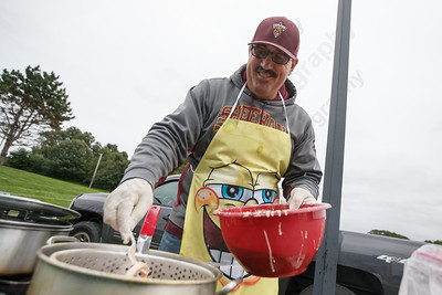 Ed Villano drops some battered onion rings for a pre-game tailgate Friday at Riccitelli Field on the campus of Sheehan High School in Wallingford September 28, 2018 | Justin Weekes / Special to the Record-Journal