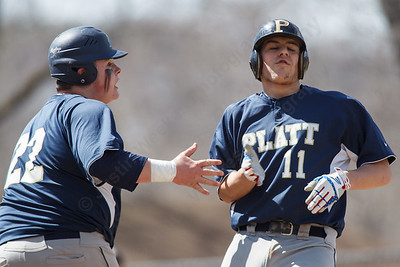 Platt's Jason Sullivan (11) and Will Kszywanos (22) high five at home plate on a two run double from Tristan Arjavich Saturday at Legion Field in Meriden Apr. 11, 2015 | Justin Weekes / For the Record-Journal