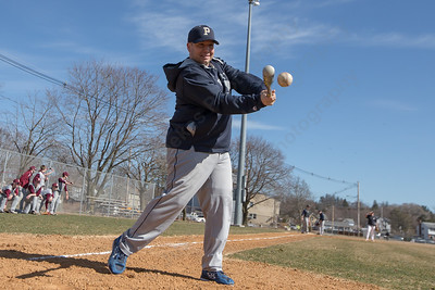 Platt's head coach Tim Redican hits infield warm-ups Thursday during a scrimmage at West Side field in Wallingford Mar. 30, 2017 | Justin Weekes / For the Record-Journal