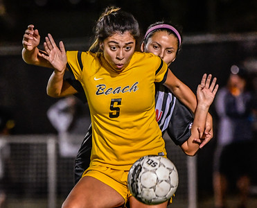 A Long Beach State player battles for the ball against Cal State Northridge