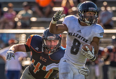 Orange Coast College #47 attempts tackle on #8 running back from Fullerton Junior College
